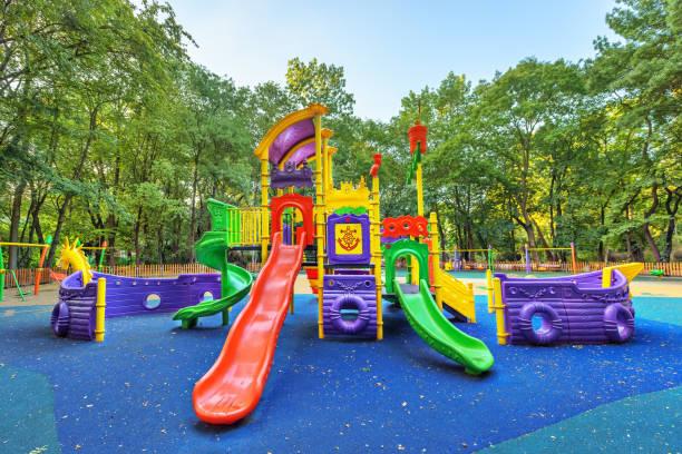 children playground on yard activities in public park surrounded by green trees at sunlight morning. - spielplatz design stock-fotos und bilder