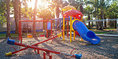 children playground with colorful swing and plastic slide on sand in public park sunlight background