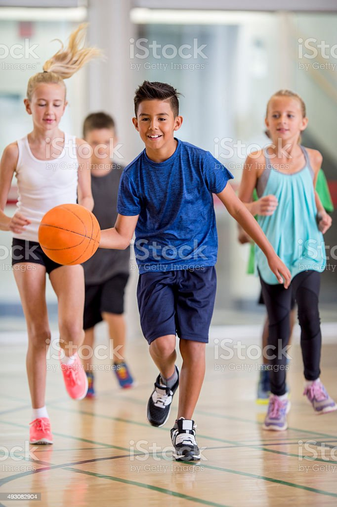 Children Playing Basketball at the Gym stock photo