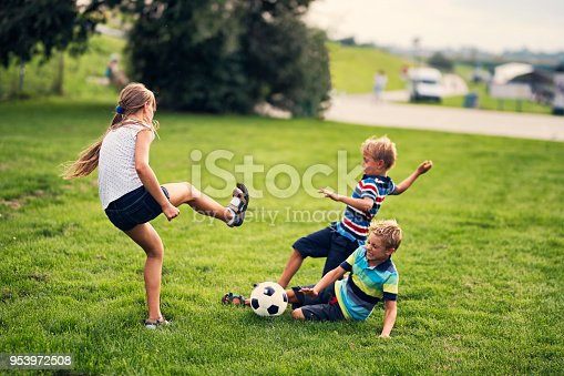 istock Children playing football on grass in city park 953972508