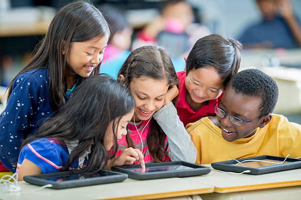 Crianças jogando jogos em um Tablet - foto de acervo