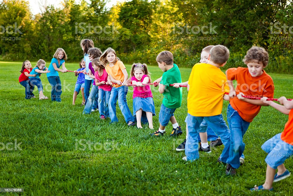 Children Playing Girls Versus Boys Tug-of-War Game Outside royalty-free stock photo