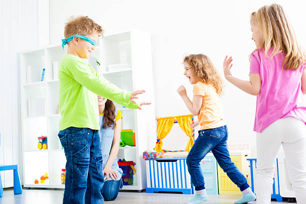 Children Playing Hide and Seek. Group of preschool children having fun playing Hide and Seek in a preschool, real action, children running and hiding. hide and seek stock pictures, royalty-free photos & images