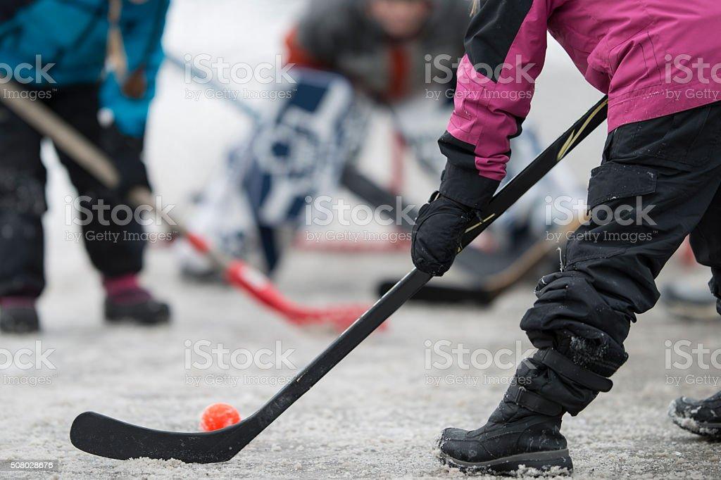 Children Playing Hockey Outdoors stock photo