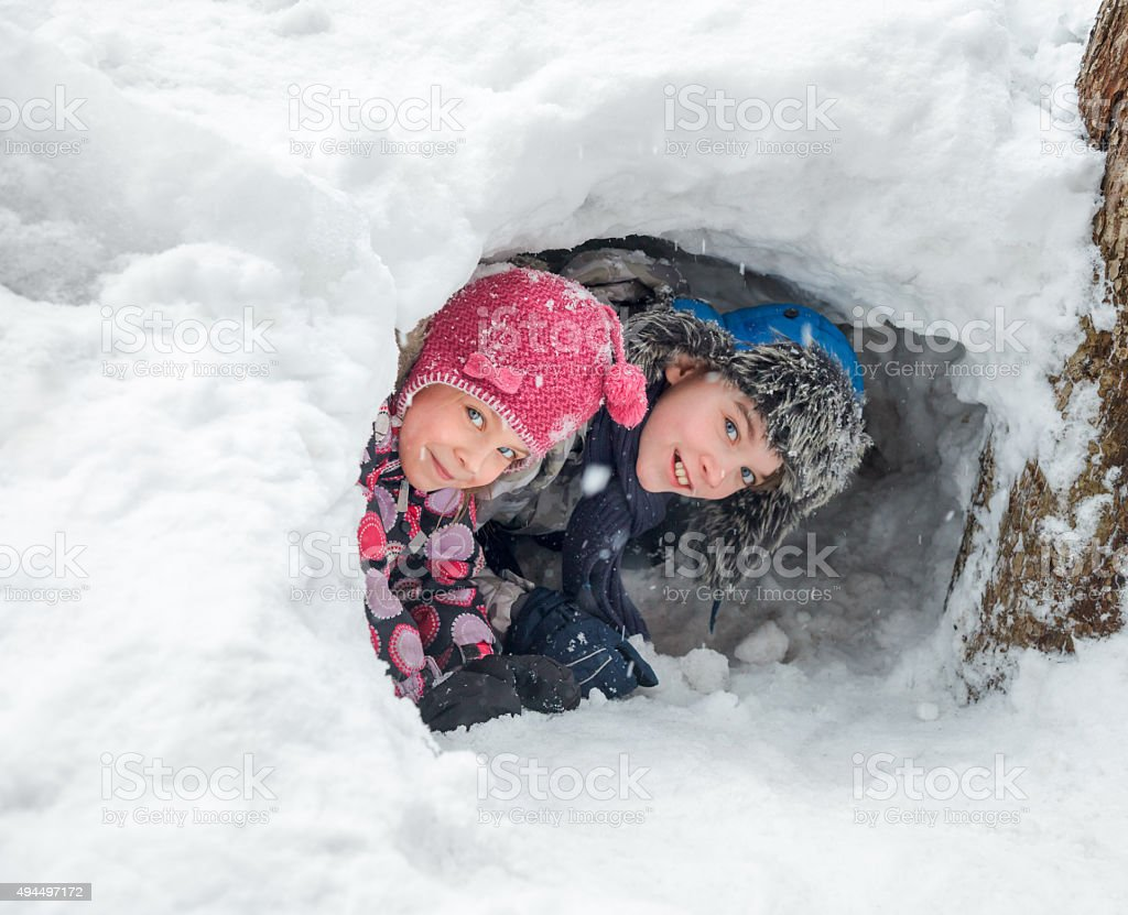 Children playing in a snow cave stock photo