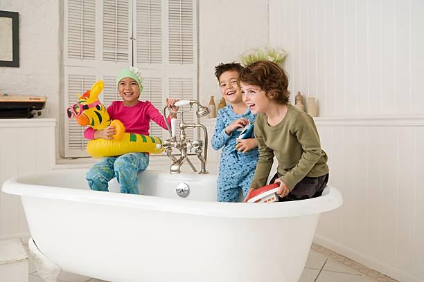 Children playing in bath tub stock photo