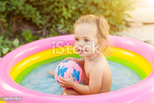 467327992istockphoto Children playing in inflatable baby pool. Kids swim and splash in colorful round pool Happy little girl playing with water toys on hot summer day. Family having fun outdoors in the backyard. 1037811510
