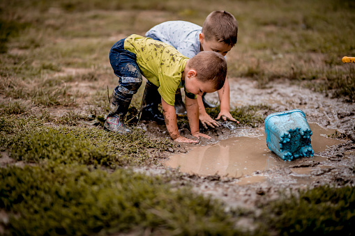 Little boys playing in muddy ponds