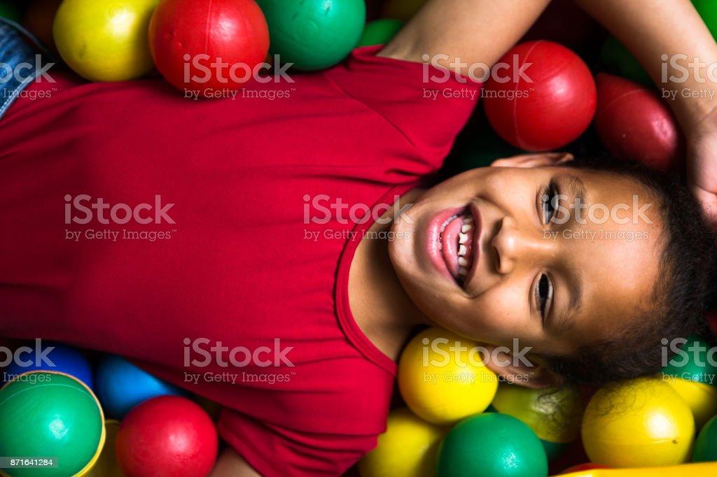 Crianças brincando no plástico da piscina bolas completa coloridas - foto de acervo