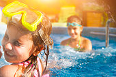 Children playing in pool. Two little girls having fun in the pool. Summer holidays and vacation concept