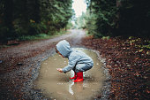 A cute group of kids wearing rain boots splash and play in a big mud puddle, enjoying the discovery and excitement of being outdoors and experiencing nature.