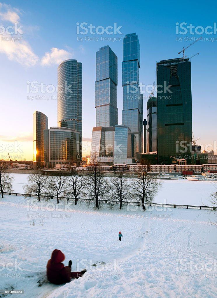 Children playing in snow at Moscow City skyscrapers royalty-free stock photo