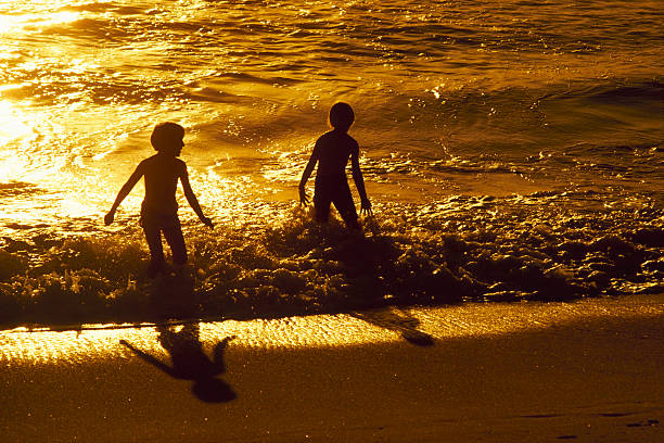 Children Playing In The Ocean stock photo