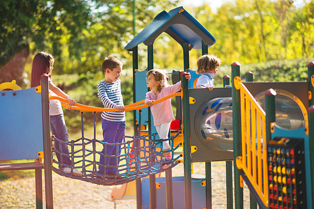 Children playing in the park at playground and communicating. Small group of children having good time at jungle gym and talking. leisure equipment stock pictures, royalty-free photos & images