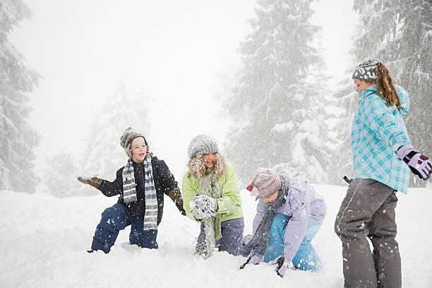 kinder spielen im schnee - schneemann bauen stock-fotos und bilder