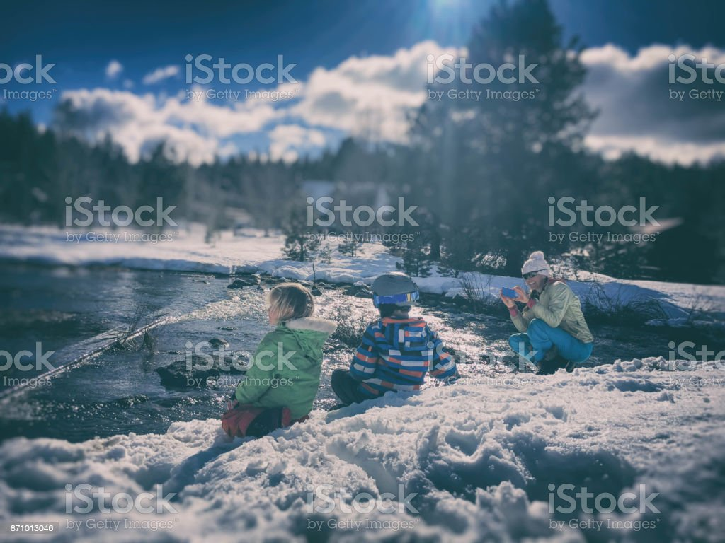 children playing in the snow while mom takes a picture stock photo