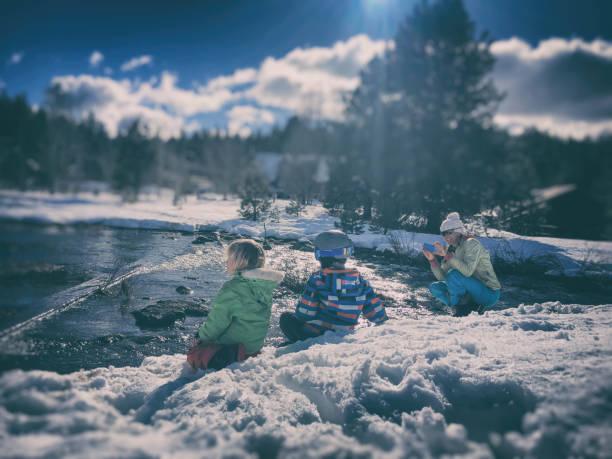 kinder im schnee spielen, während mama ein bild nimmt - lake tahoe winter stock-fotos und bilder