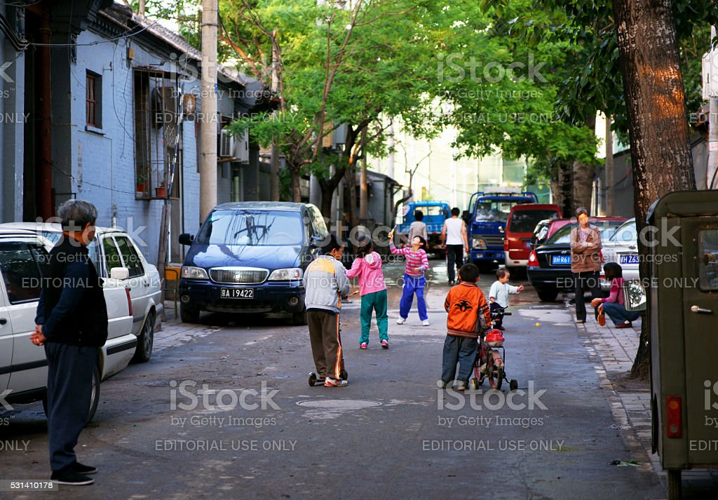 Children Playing on A Historic Beijing Hutong Street at Sunset stock photo