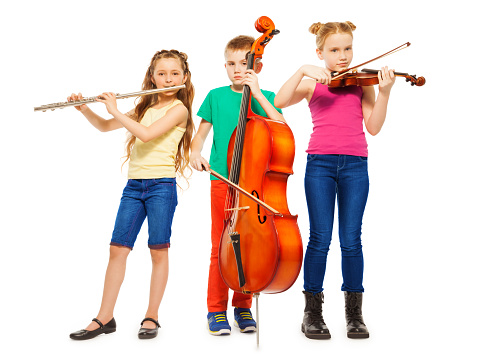 Children playing on musical instruments together on white background