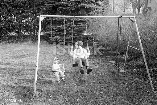 Two little boys playing on back yard swing set in the autumn of 1965. Waterloo, Iowa, USA. Scanned film.