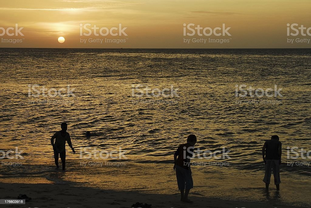 Children playing on the beach at sunset royalty-free stock photo
