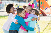 A multi-ethnic group of children playing outdoors on a playground on a sunny day. They are all playfully hugging each other.
