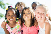 A multi-ethnic group of elementary age children are standing together outside on a beautiful sunny day.