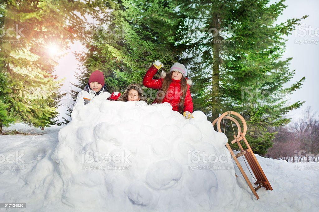 Children playing snowballs in winter forest stock photo