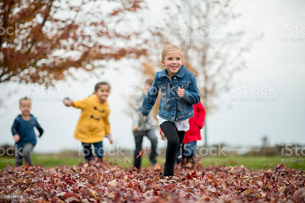 Children Playing Tag in the Leaves stock photo