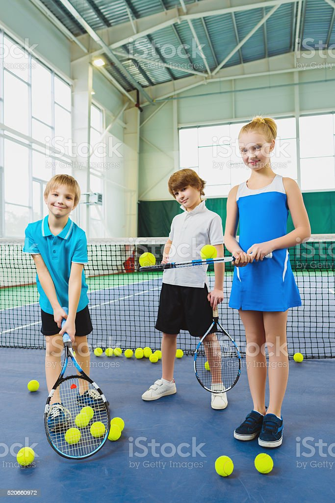 Children playing tennis and posing indoor stock photo