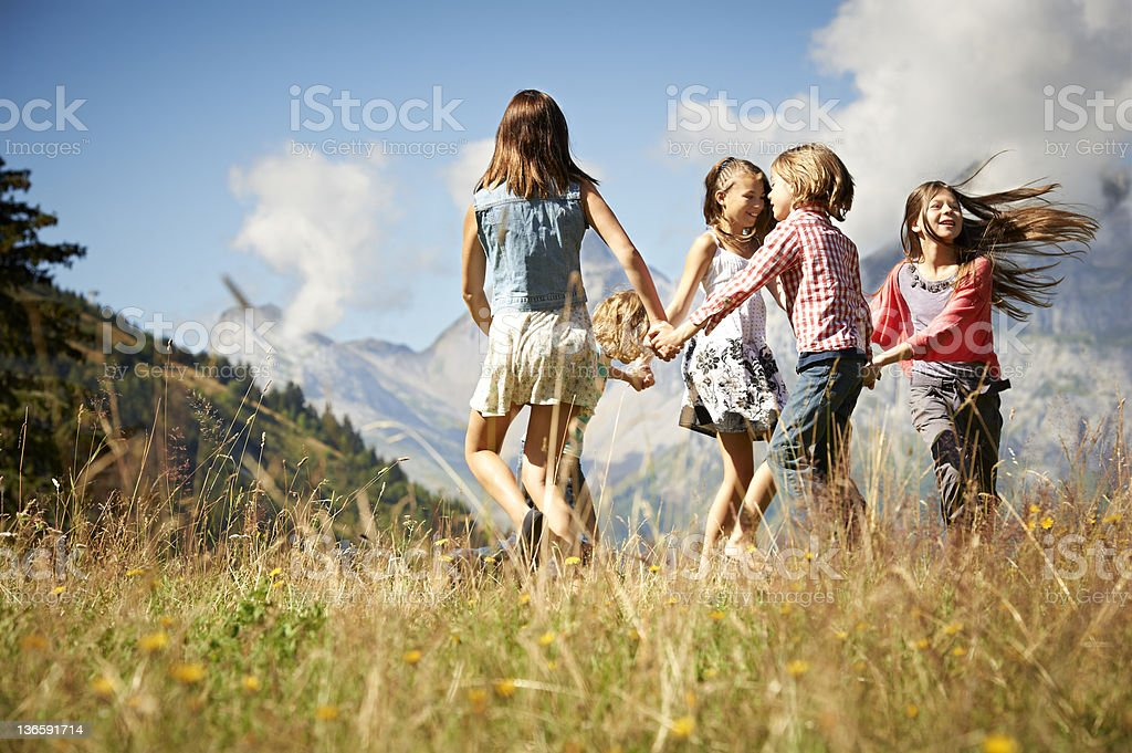 Children playing together in field stock photo