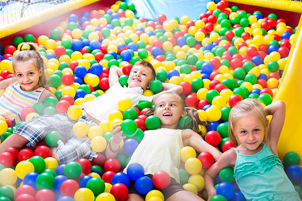 children playing together in pool with plastic multicolored ball - Photo