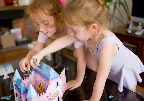Children playing together with doll house stock photo