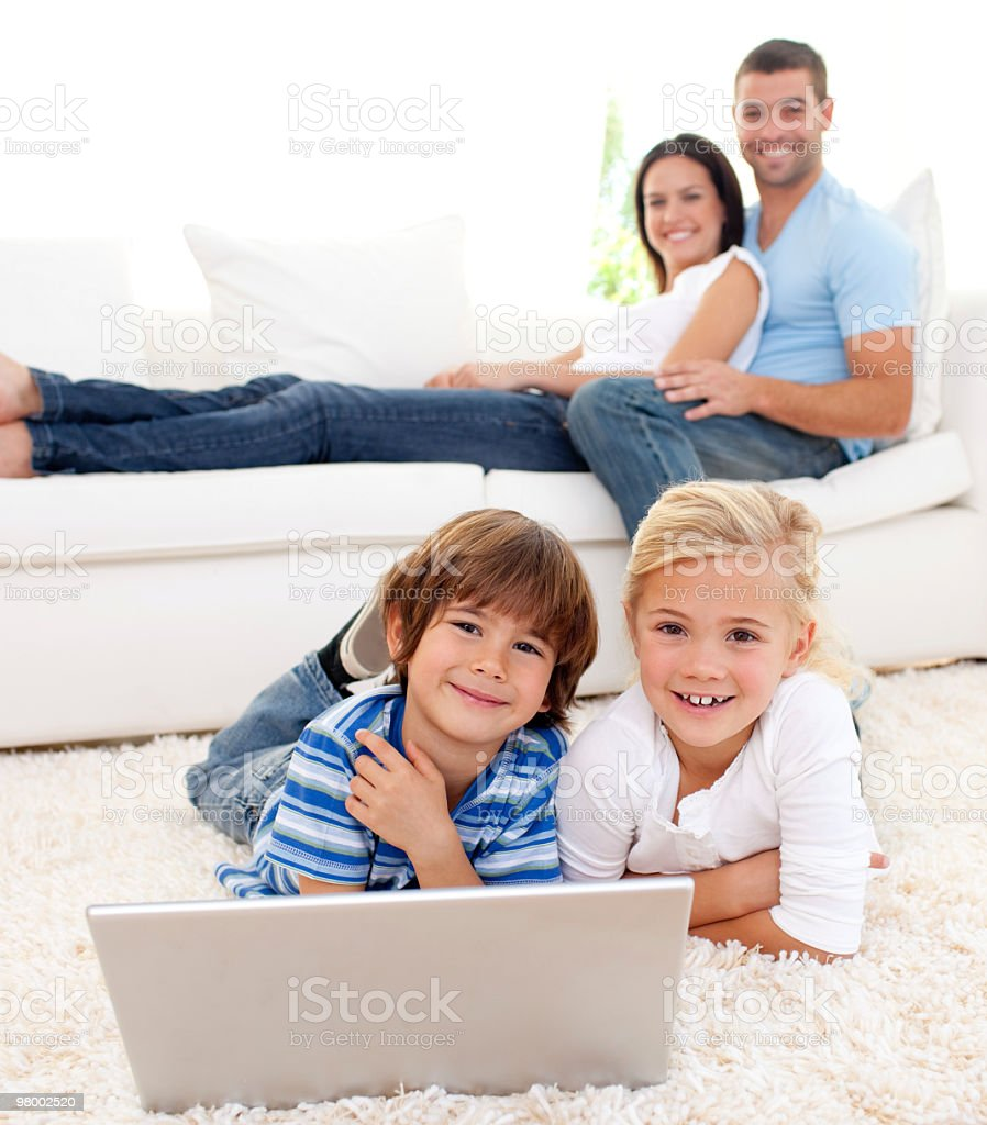 Children playing with a laptop on floor royalty-free stock photo