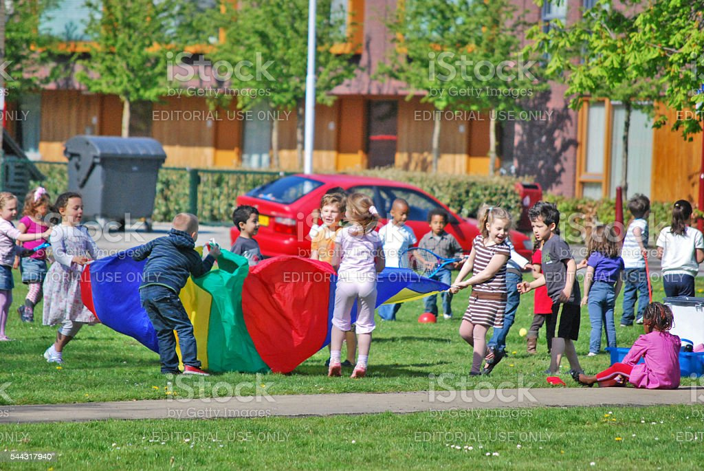 Children playing with a large blanket, Voorburg, The Netherlands stock photo
