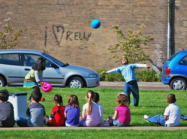 Children playing with balls, Voorburg, The Netherlands Voorburg, The Netherlands - April 27, 2010: Children playing with balls infront of a brick wall with graffiti reading I Heart Kelly in Voorburg, Netherlands voorburg stock pictures, royalty-free photos & images