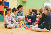 Group of children playing with blocks in kindergarten with their teacher. Showing their imagination and skill and creativity. Sitting on the floor and holding blocks in their hands. Kids are playing and smiling. Teacher is sitting in the middle and helping them to create buildings from blocks.