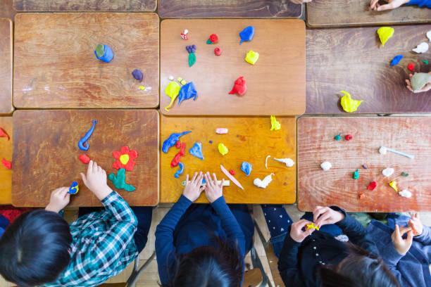 dzieci bawiące się gliną w klasie - glina zdjęcia i obrazy z banku zdjęć