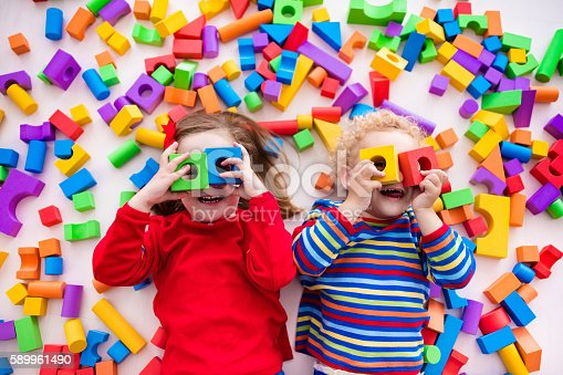 istock Children playing with colorful blocks building a block tower 589961490