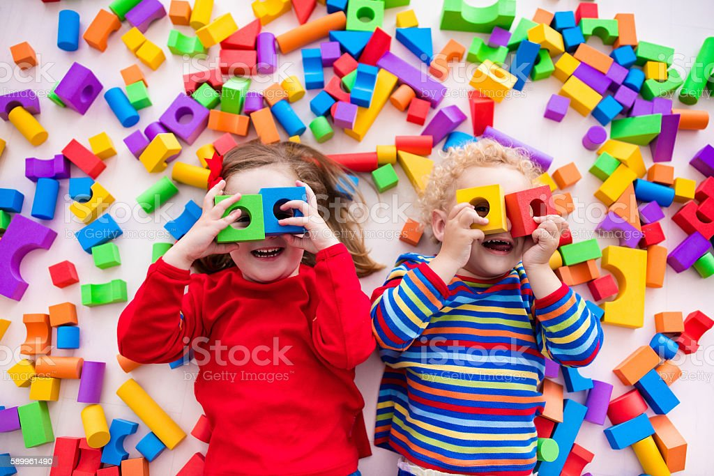 Children playing with colorful blocks building a block tower - foto stock