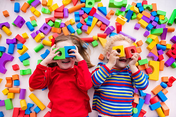 Children playing with colorful blocks building a block tower stock photo