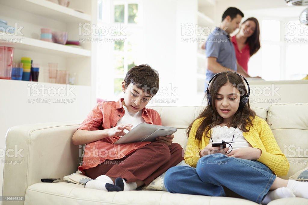 Niños jugando con dispositivos digitales como los padres hacen de comida - foto de stock