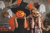 Boy and a girl are playing at the Halloween party, covering their faces with Jack O'Lantern bucket and paper bag.