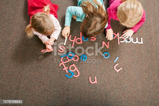 Children playing with letter shapes in grade school classroom