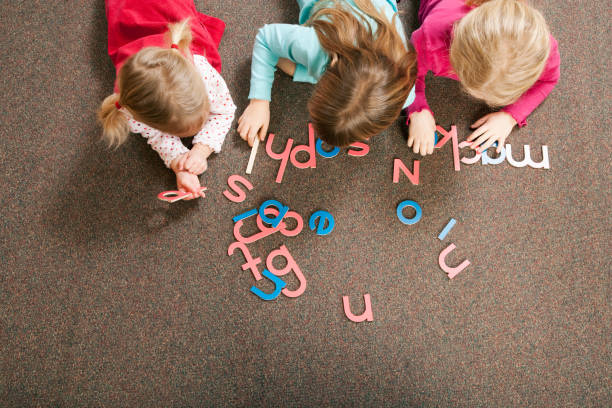 Children playing with letter shapes in grade school classroom Children playing with letter shapes in grade school classroom spelling stock pictures, royalty-free photos & images