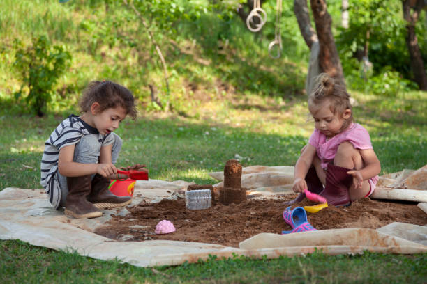 Children playing with sand in the backyard stock photo
