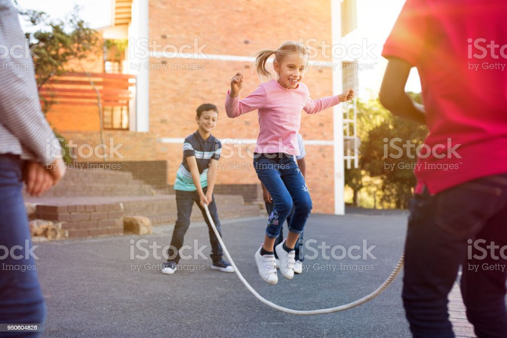 Children playing with skipping rope stock photo
