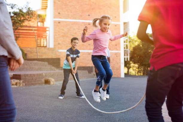 children playing with skipping rope - infanzia foto e immagini stock