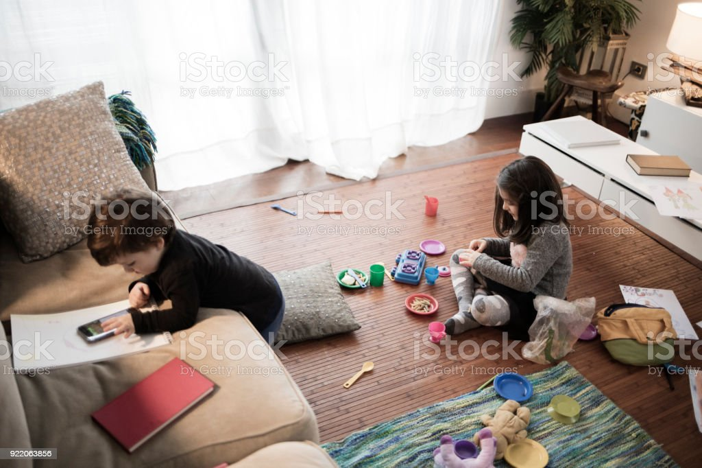 Children playing with smartphone and traditional toys at home