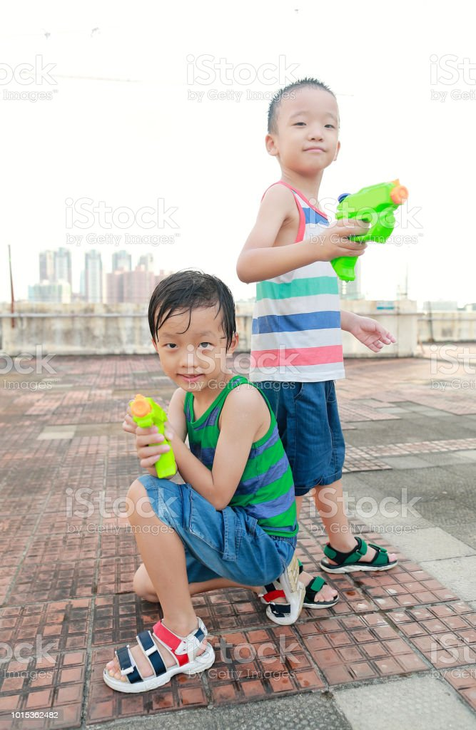 Children playing with squirt gun - Stock image .